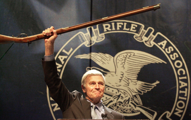 "NRA President Charlton Heston holds up a musket as he tells the 5,000-plus members attending an NRA annual meeting in Charlotte, NC, in May, 2000, that they can have his gun when they pry it ""from my cold dead hands."" (AP Photo/Ric Feld)"