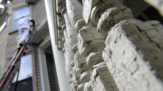 The lead paint flakes and cracks on the spindles of a porch as a painter sands the siding of a house. (AP Photo/Stew Milne)