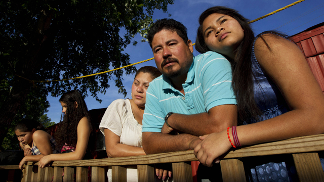 Diane Martell, 17, right, leans on her parents Maurcio and Guadalupe on the porch of their home in Bessemer, Ala. The Martells are illegal immigrants, as are most of the residents of this trailer park, and they live in fear of Alabama's harsh immigration laws. (AP Photo/Dave Martin, File)