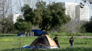 San Jose city workers Mark Ruffing, left, and Rita Tabaldo attach eviction notices to a tent at a tent city in San Jose, Calif., Tuesday, March 5, 2013. (AP Photo/Jeff Chiu)