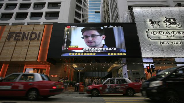 A TV screen shows a news report of Edward Snowden at a shopping mall in Hong Kong Sunday, June 23, 2013. (AP Photo/Vincent Yu, File)