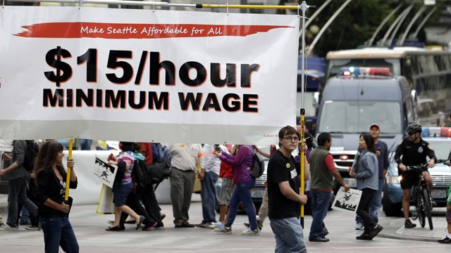 Demonstrators protesting for $15/hour wages and proper treatment for fast-food workers march in downtown Seattle. (AP Photo/Elaine Thompson, File)