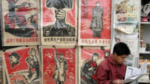 A merchant at a Beijing flea market sits beside copies of propaganda posters from China's ultraleftist 1966-76 Cultural Revolution on Sunday, May 21, 2006. This year marks the 40th anniversary of the start of the upheaval inspired by then-Chinese leader Mao Zedong, in which millions of people were persecuted.  (AP Photo)