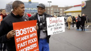 Pedro Rodriguez, right, talks with Andrus Reyes as they participate in a demonstration on a Burger King parking lot as part of a nationwide protest supporting higher wages for workers in the fast-food industry and other minimum wage jobs in Boston, Thursday, Dec. 5, 2013. (AP Photo/Stephan Savoia)