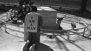 A striking Atlanta sanitation worker kneels at the grave of Dr. Martin Luther King Jr. after a rally by Southern Christian Leadership Conference supporting the strike in Atlanta on April 4, 1970. King was killed in Memphis, Tenn., while supporting a sanitation workers' strike there in 1968. The picket signs reading 'I Am A Man' were first used in the Memphis strike. (AP Photo/BJ)
