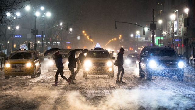 Pedestrians cross 34th Street and 6th Avenue under falling snow in Herald Square, Thursday, Jan. 2, 2014, in New York. The storm is expected to bring snow, stiff winds and punishing cold into the Northeast. (AP Photo/John Minchillo)