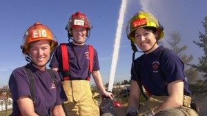 Tacoma Fire Dept. firefighters Gayle Nikolaisen, left, Lt. Jennifer Gunnell and Karen Leming pose atop their fire engine Sunday, March 3, 2002. (AP Photo/Elaine Thompson)