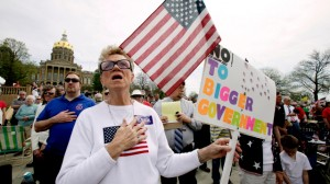 Kay Hohler, of West Des Moines, Iowa, sings the national anthem before the start of a tea party rally on the steps of the Iowa Statehouse, Thursday, April 15, 2010, in Des Moines, Iowa. (Photo by Charlie Neibergall/AP)