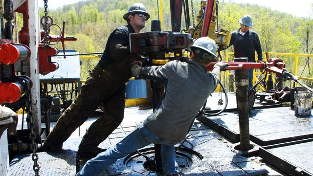 """FILE - In this April 23, 2010 file photo, workers move a section of well casing into place at a Chesapeake Energy natural gas well site near Burlington, Pa., in Bradford County. So vast is the wealth of natural gas locked into dense rock deep beneath Pennsylvania, New York, West Virginia and Ohio that some geologists estimate it's enough to supply the entire East Coast for 50 years. But freeing it requires a powerful drilling process called hydraulic fracturing or """"fracking,""""using millions of gallons of water brewed with toxic chemicals that some fear threaten to pollute water above and below ground, deplete aquifers and perhaps endanger human health and the environment. (AP Photo/Ralph Wilson, File)"""