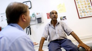 Patient Luis Gutierrez, right, talks with Dr. Javier Hiriart at Camillus Health Concern, Wednesday, June 27, 2012, in Miami. (AP Photo/Lynne Sladky)