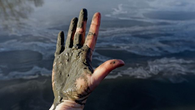 Hand covered with wet coal ash from the Dan River swirling in the background as state and federal environmental officials continued their investigations of a spill of coal ash into the river in Danville, Va., Wednesday, Feb. 5, 2014. Duke Energy estimates that up to 82,000 tons of ash has been released from a break in a 48-inch storm water pipe at the Dan River Power Plant in Eden N.C. on Sunday. (AP Photo/Gerry Broome)
