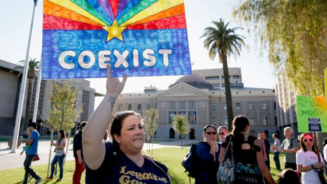 Jo Beaudry holds up a sign as she joins nearly 250 gay rights supporters protesting SB1062 at the Arizona Capitol, Friday, Feb. 21, 2014, in Phoenix. The protesters gathered demanding Gov. Jan Brewer veto legislation that would allow business owners to refuse to serve gays by citing their religious beliefs. (AP Photo/Ross D. Franklin)