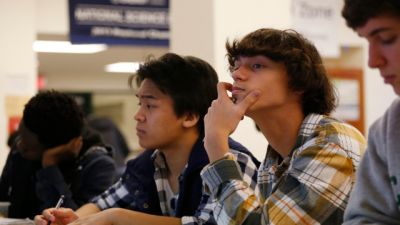 EMBARGOED FOR RELEASE AT 3 A.M. EST (5 P.M. JST) - Students Julian Lopez, 12th grade, second left; Ben Montalbano, 11th grade, second right; and James Agostino, 12th grade, right; listen during their Advanced Placement (AP) Physics class at Woodrow Wilson High School in Washington, Friday, Feb. 7, 2014. (AP Photo/Charles Dharapak)