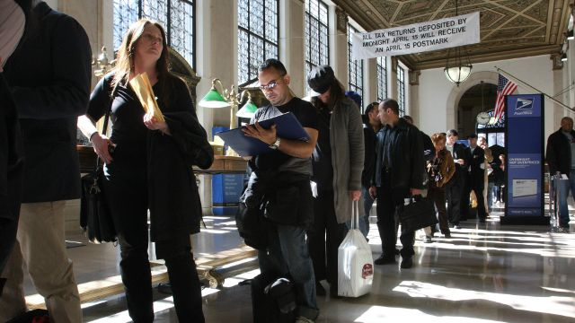 In this April, 15, 2008, file photo, Jackie Doyle, of Greenwood Lake, N.Y., second from left, waits in line to mail her husband's taxes at the James A. Farley Main Post Office in New York. (AP Photo/Tina Fineberg, File)