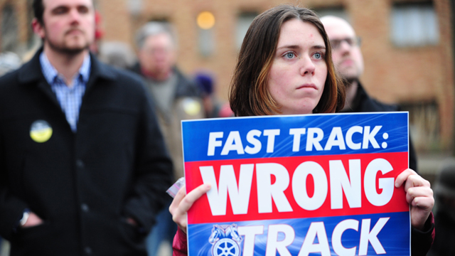 A protester holds a sign against the fast-track authority for the TPP during a protest in Portland, Oregon, on January 31, 2014. (Photo by Alex Milan Tracy/NurPhoto/Sipa USA) (Sipa via AP Images)