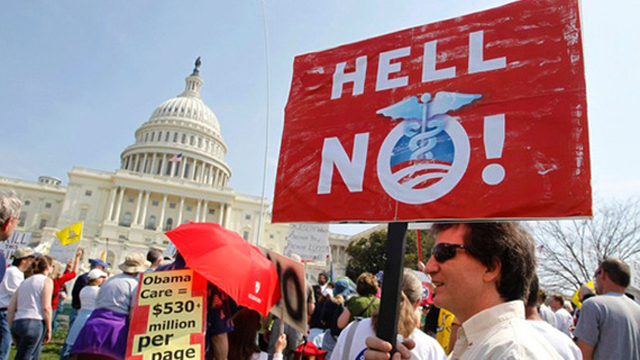 A protestor holds up a sign that says 'Hell No Obamacare' at a rally