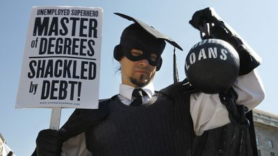 "HOLD FOR RELEASE UNTIL 12:01 A.M. EDT. THIS PHOTO MAY NOT BE PUBLISHED, BROADCAST OR POSTED ONLINE BEFORE 12:01 A.M. EDT. - In this Oct. 6, 2011 photo, Gan Golan, of Los Angeles, dressed as the ""Master of Degrees,"" holds a ball and chain representing his college loan debt, during Occupy DC activities in Washington. As President Obama prepared to announce new measures Wednesday to help ease the burden of student loan debt, new figures painted a demoralizing picture of college costs for students and parents: Average in-state tuition and fees at four-year public colleges rose an additional $631 this fall, or 8.3 percent, compared with a year ago. (AP Photo/Jacquelyn Martin)"