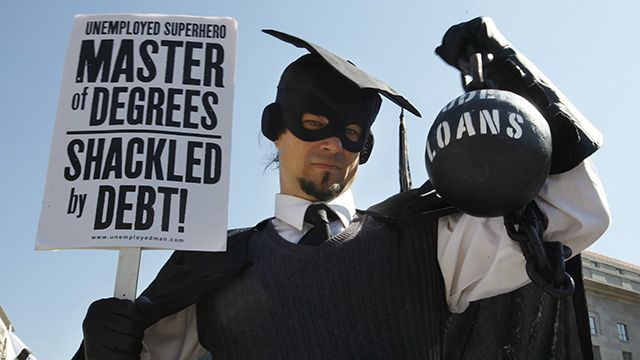 """HOLD FOR RELEASE UNTIL 12:01 A.M. EDT. THIS PHOTO MAY NOT BE PUBLISHED, BROADCAST OR POSTED ONLINE BEFORE 12:01 A.M. EDT. - In this Oct. 6, 2011 photo, Gan Golan, of Los Angeles, dressed as the """"Master of Degrees,"""" holds a ball and chain representing his college loan debt, during Occupy DC activities in Washington. As President Obama prepared to announce new measures Wednesday to help ease the burden of student loan debt, new figures painted a demoralizing picture of college costs for students and parents: Average in-state tuition and fees at four-year public colleges rose an additional $631 this fall, or 8.3 percent, compared with a year ago. (AP Photo/Jacquelyn Martin)"""