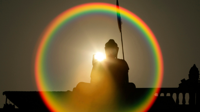 In this Monday, Jan. 28, 2013 photo, a Buddha statue is silhouetted by the sun on the hill of Phmon Baseth, outskirt of Phnom Penh, Cambodia. (AP Photo/Heng Sinith)
