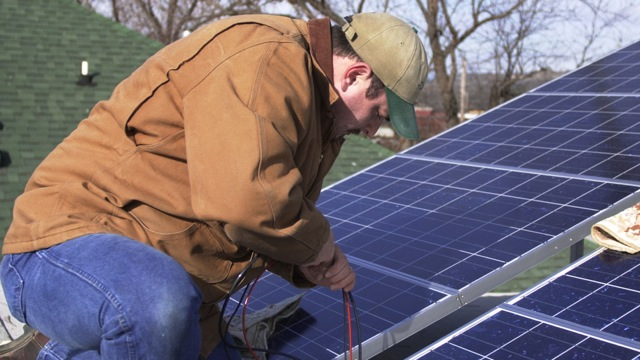 Ben Gerald from Staley Electric Co. helps install solar power panels on the roof of a house in North Little Rock, Arkansas on Jan. 22, 2003. (AP Photo/David Quinn)