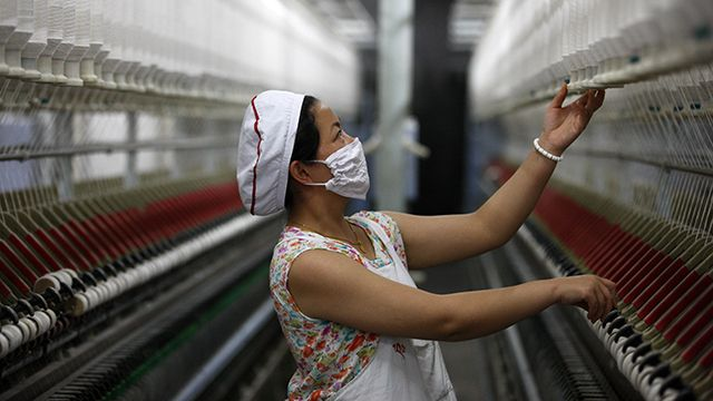 A female Chinese worker handles production of yarn to be exported to South Korea at a textile factory in Huaibei city, east Chinas Anhui province, 16 April 2014.