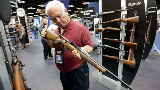 Jerry Miller, of Georgetown, Texas, looks over a rifle at the National Rifle Association's annual convention on Friday, April 25, 2014 in Indianapolis. (AP Photo/AJ Mast)