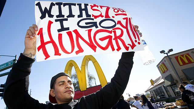 Alex Robles protests against low wages for fast-food workers in front of a McDonald's on Thursday, December 5, 2013, in Phoenix. (AP Photo/Ross D. Franklin)