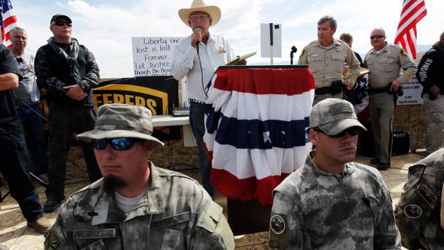 Rancher Cliven Bundy, middle, addresses his supporters along side Clark County Sheriff Doug Gillespie, right, on April 12, 2014. (AP Photo/Las Vegas Review-Journal, Jason Bean)