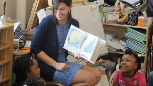 In this April 10, 2014 file photo, student teacher Franchesca Moreno, 21, reads to Andreanna Thomas, 6, right, and Alana Cawthon, upper left, at Bennett Park Montessori School in Buffalo, NY. (AP Photo)