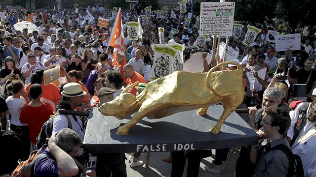 A replica of the iconic Wall Street bull is lifted as a symbol of greed during a protest rally to support low-wage workers as part of National Day of Action in New York, Tuesday, July 24, 2012. (AP Photo/Bebeto Matthews)