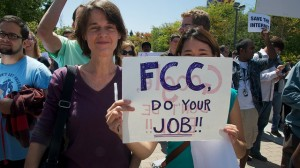 Two women hold up a sign that says 'FCC, Do your Job!' at a rally at Google headquarters.