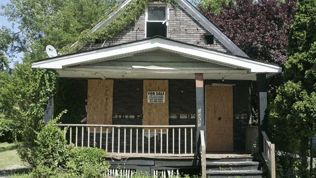 """In this photo taken on Tuesday, July 14, 2009, a """"For Sale"""" sign rests on a vacant house in Cleveland. (AP Photo/Tony Dejak)"""
