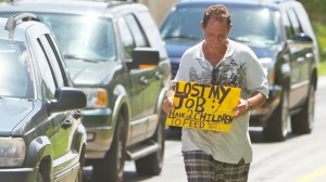 a man who did not wish to be identified, who lost his job two months ago after being hurt on the job, works to collect money for his family on a Miami street corner. (AP Photo/J Pat Carter, File)