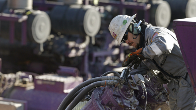 In this March 25, 2014 photo, a worker oils a pump during a hydraulic fracturing operation at an Encana Corp. well pad near Mead, Colo. (AP Photo/Brennan Linsley)