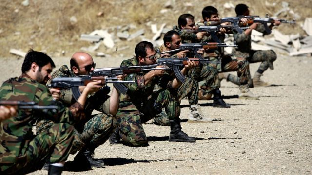 Members of the Basij paramilitary militia fire their weapons during a training session, in Tehran, Iran. The Basij has its roots as volunteer fighters during the 1980-88 war with Iraq. I