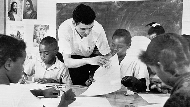 """this Aug. 23, 1964 file photo, Bruce Solomon, of the Brooklyn borough of New York, teaches a class for young black students about arts, African American history and rights at a """"Freedom School"""" in Jackson, Miss."""