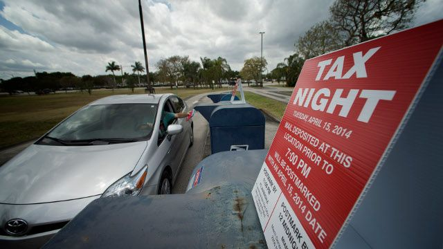 There was a steady stream of post office customers dropping off mail including their tax forms at the Pembroke Pines, Fla., Tuesday, April 15, 2014. The post office placed signs on the mail boxes to inform patrons about times. (AP Photo/J Pat Carter)