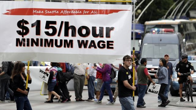 In this Aug. 1, 2013 photo, demonstrators protesting what they say are low wages and improper treatment for fast-food workers march in downtown Seattle. Washington already has the nation's highest state minimum wage at $9.19 an hour. Now, there's a push in Seattle, at least, to make it $15. That would mean fast food workers, retail clerks, baristas and other minimum wage workers would get what protesters demanded when they shut down a handful of city restaurants in May and others demonstrated nationwide in July. (AP Photo/Elaine Thompson)