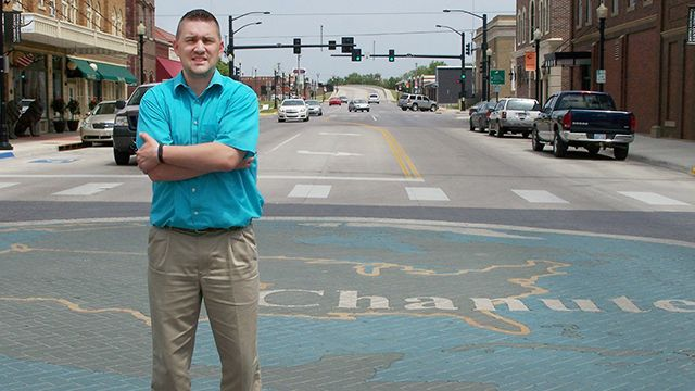 Chanute Mayor Greg Woodyard stands on a brick mosaic of the Google Earth logo at the intersection of Lincoln and Main streets on May 21, 2014. on May 19, 2014 in Chanute, Kan.