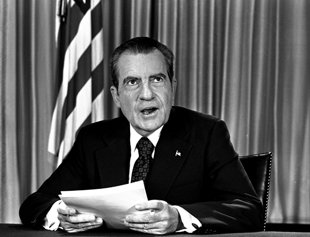 President Nixon sits in his White House office, August 16, 1973, as he poses for pictures after delivering a nationwide television address dealing with Watergate. (AP Photo)