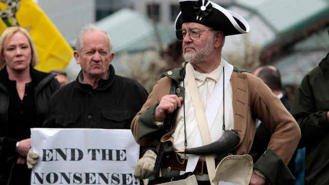 Mike Challenger, of Bothell, Wash., applauds a speaker as he stands dressed in Revolutionary-period wear at a tax day tea party rally of about a hundred protesters Friday, April 15, 2011, in Bellevue, Wash. (AP Photo/Elaine Thompson)