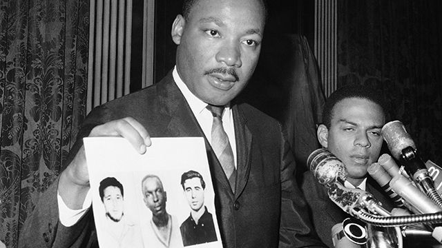 Dr. Martin Luther King displays pictures of three civil rights workers,who were slain in Mississippi the summer before, from left Michael Schwerner, James Chaney, and Andrew Goodman, at a news conference in New York. (AP Photo/JL, File)