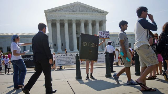 A demonstrator dressed as the Bible stands outside the Supreme Court in Washington, June 30, 2014, awaiting the court's decision on the Hobby Lobby case. (AP Photo/Pablo Martinez Monsivais)