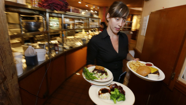 In this June 2, 2014 photo, Wendy Harrison, a waitress at the icon Grill in Seattle, carries food to a table as she works during lunchtime. An Associated Press comparison of the cost of living at several other major U.S. cities found that a $15 minimum wage, like Seattle adopted this week, will make a difference, but won't buy a lavish lifestyle. (AP Photo/Ted S. Warren)