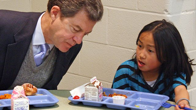 n this Jan. 23, 2014 file photo Kansas Gov. Sam Brownback, left, leans in to listen to Xen Hesse as the two each lunch at Roesland Elementary School in Roeland Park, Kan. On Friday, March 7, 2014, the Kansas Supreme Court said the state's current public school funding levels are unconstitutional. The case has broader implications beyond the classroom: Kansas enacted sweeping cuts to income taxes championed by Brownback that have reduced the amount of available resources to comply with a court order. (AP Photo/John Milburn, File)