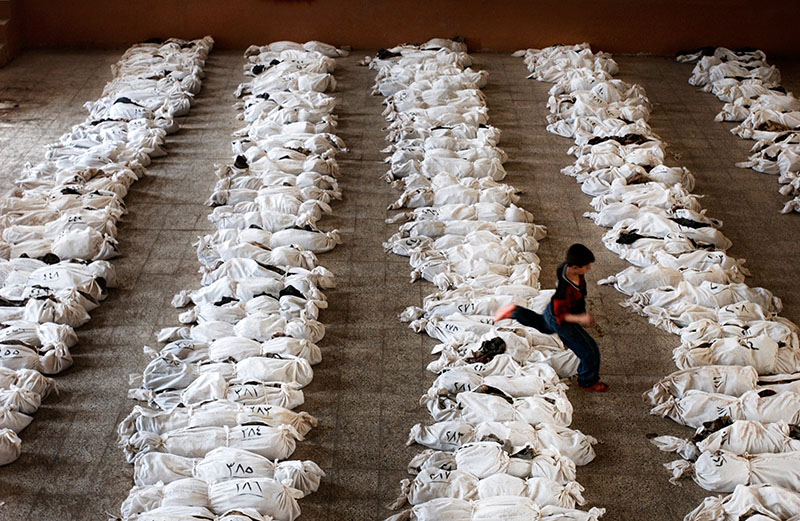 An Iraqi child jumps over the remains of victims found in a mass grave south of Baghdad in Al Musayyib on May 27, 2003. The bodies had been brought to this school for identification by family members who searched for identity cards and other clues among the skeletons. The victims were killed by Saddam Hussein'€™s government following a Shi'€™ite uprising here. (Marco Di Lauro/Getty Images.)