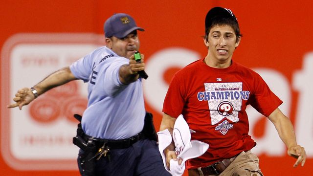 A law enforcement officer chases down Steve Consalvi, who ran on to the field before the eighth inning of a baseball game between the Philadelphia Phillies and the St. Louis Cardinals, Monday, May 3, 2010, in Philadelphia. St. Louis won 6-3. The officer used a Taser gun to apprehend Consalvi. (AP Photo/Matt Slocum)