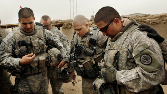In this Tuesday, Jan. 25, 2011 file photo, U.S. Army Lt. Daniel McCord, left, Staff Sgt. Marc Krugh, center and Sgt. Christopher Torrentes, right, from the 3rd Armored Cavalry Regiment pray before heading out on a patrol at Contingency Operating Site Kalsu, south of Baghdad, Iraq. (AP Photo/Maya Alleruzzo, File)