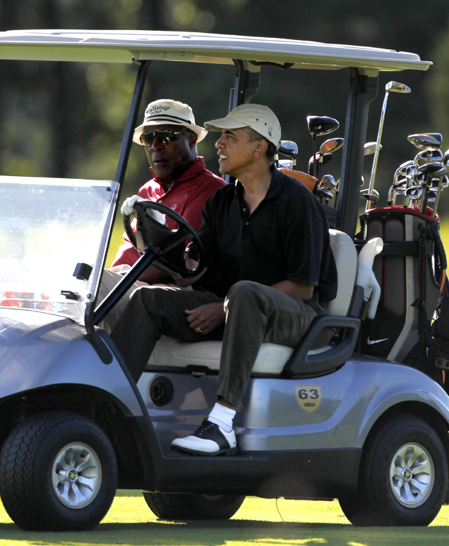 President Barack Obama, right, drives a golf cart with businessman Vernon Jordan, left, while playing golf at Farm Neck Golf Club, in Oak Bluffs, Mass., on the island of Martha's Vineyard, Tuesday, Aug. 23, 2011. (AP Photo/Steven Senne)