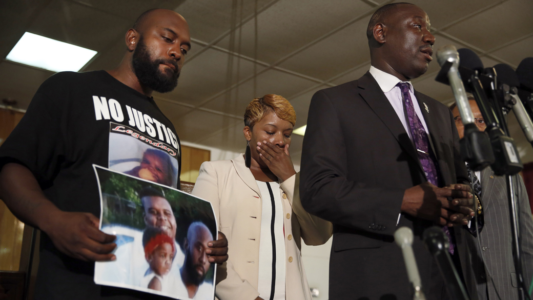 """Lesley McSpadden, center, and Michael Brown Sr., left, the parents of Michael Brown, listen as attorney Benjamin Crump speaks during a news conference in Jennings, Missouri on Aug. 11, 2014. Crump set up the """"Michael Brown Memorial Fundî on behalf of the family of the black 18-year-old that has raised almost $279,000 since Brown was shot Aug. 9 by white police officer Darren Wilson. (AP Photo/Jeff Roberson, File)"""